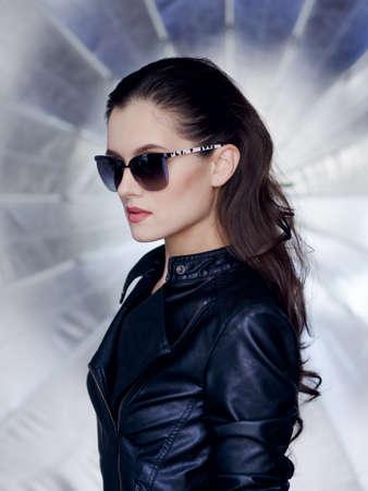 Confiant et brune avec un beau visage, des lunettes de soleil noires élégantes, une veste en cuir noire et une coiffure rebelle regarde d'un côté avec attitude. Vue verticale sur fond argenté brillant.