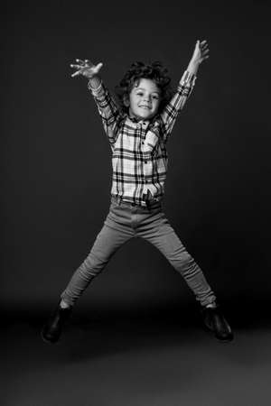 Frontal portrait of a jumping boy with to the side his arms and legs, shows his joy, happiness kid concept, freedom. Black and white image. isolated on a black background.