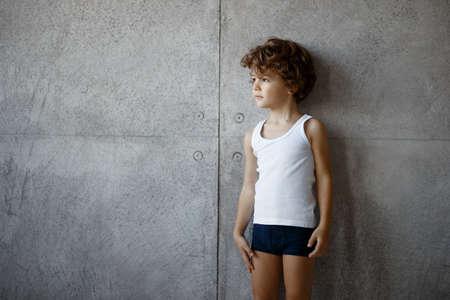 Profile portrait of a handsome little boy in underwear posing on concrete wall, lokking a one side, copy space.