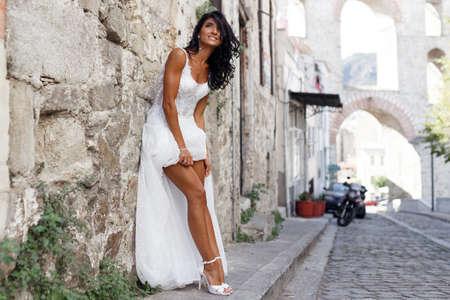 Gorgeous bride in a sexy white dress near old greece city, showing his sensual legs, poses near white stone wall in street in summer time. Travel, wedding abroad. Copy space.