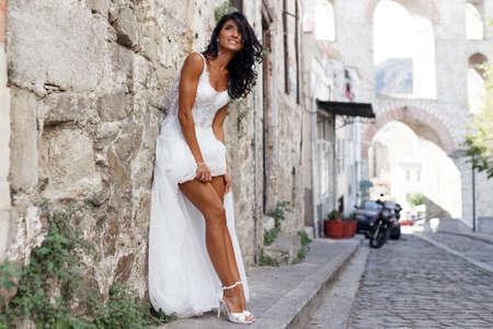 Superbe mariée vêtue d'une robe blanche près de la vieille ville de Grèce, montrant ses jambes sensuelles, pose près d'un mur de pierre blanche dans la rue en été. Voyage, mariage à l'étranger. Espace de copie.