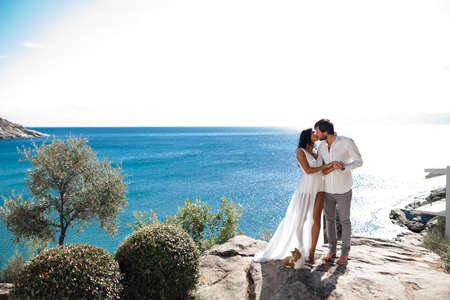 Two lovers kiss and embrace a coast behind the Mediterranean Sea during summer vacation time for couple in Greece.