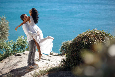 Romantic couple embracing and kissing, behinde beautiful seascape of a mediterrianean sea in Greece.