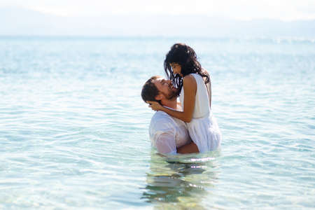 Happy couple enter in water in clothing, have funny moments, copy space.