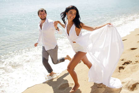 Smiling couple run on beach, in wedding clothing, enjoying in honeymoon, in summer time, sunny day, holiday, Greece.