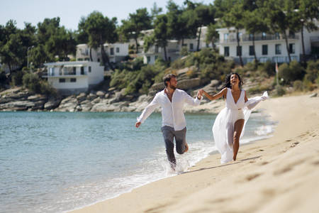 Happy romantic couple hold their hands and go on the beach in Greece, the honeymoon vacation, the perfect sunny day in the summer. Stock Photo