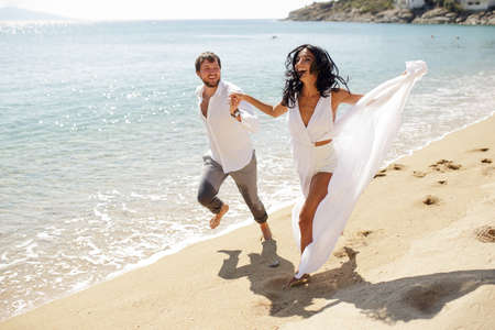 Young people run on hot sand couple in honeymoon on Greece, smiling and run on the beach, summer time, sunny day.