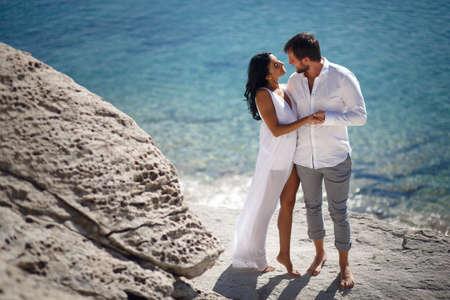 Elegant gentle stylish groom and bride near mediterranean sea on stones beach. Wedding couple in love.