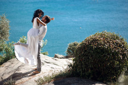 Romantic couple embracing and kissing, isolated on a blue mediterranean sea background.