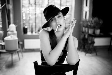 Beauty portrait of a smoking young woman in black hat, sitting on chair, keeping her hands near face, isolated on a blurry interior room, behind a window. Black and white image.