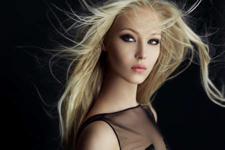 Attractive blonde girl in perfect make up with hair scattered by the wind, isolated on a black background.