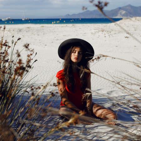 Schönheitsporträt eines sexy, heißen Brunette weibliches junges Modell mit geschlossenen Augen, posiert auf weißem Sand im roten Badeanzug mit schwarzem Hut, auf der Insel Korsika, Frankreich. Horizontale Ansicht.