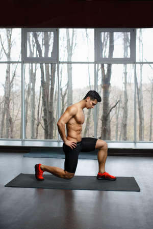Fit, muscular, athletic young man shirtless in sportswear doing strength exercise with legs in gym, isolated on a big window background. Sportly concept.