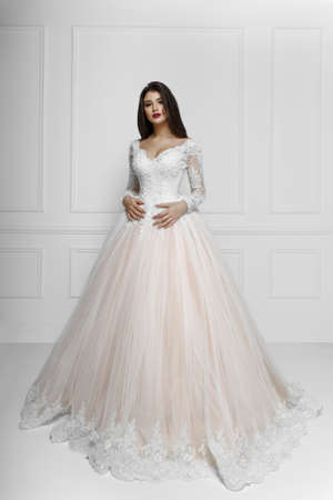 Fronatl portrait of bride with long hair, wearing elegant wedding dress with luxury make-up and hairstyle, studio indoor photo.