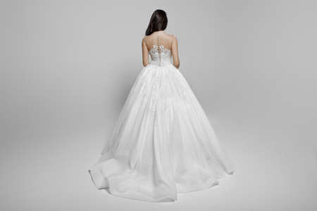 Rear view of a beautiful young woman in wedding white princess dress, isolated on a white background. Horizontal view.