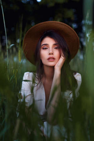 Beautiful Young Woman seated in the field in green grass, looking at camera with attitudine. Outdoors. Enjoy Nature. Healthy look girl on spring lawn. Allergy free concept. Freedom.