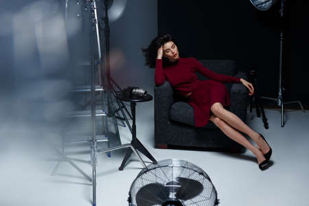 Beauty concept. Woman seated on chair, posing with closed eyes, props cinema decoration. Horizontal indoors shot. 写真素材