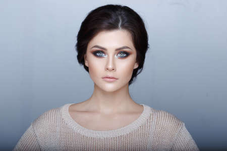 Frontal portrait of a brunette girl with beautiful light-green eyes, fresh makeup and glossy skin looking at camera, on the grey background. Horizontal view Stock Photo