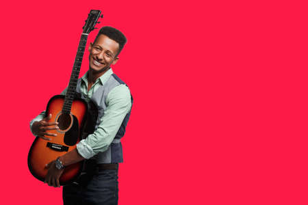 Frontal view of a happiness mixed race young man, embrace his guitar, player on blue background. Place with copy space