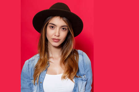 Close up portrait of a fashionable female model, wearing in casual hat and denim shirt, looking with attitude on camera, isolated over red background. Imagens