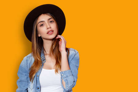 Frontal portrait of cheerful young woman in hat and denim, posing in studio with attitude looking at camera, touching her hair with hand, isolated on a yellow background.