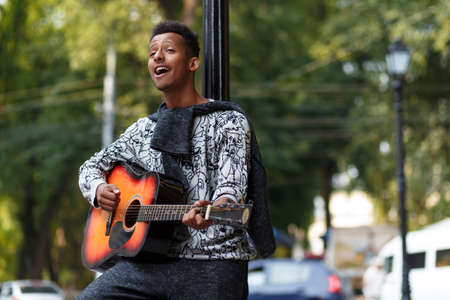 Profile of a happy young musician played on guitar, standing near street lamp sing a song in sunny day, isolated on a blurred street background. Place with copy space.