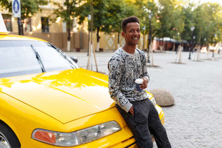 Mixed race young man drinking a coffee seated on the hood of a taxi, looking to one side, isolated on a street background, copy space. Imagens