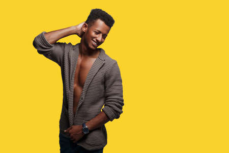 Handsome mixed race man posing amusing in brown cardigan, with naked torso, shot in studio, isolated on a yellow background. Place with copy space.