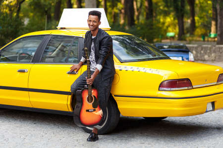 A cheerful mixed race man with guitar in casual clothes near yellow taxi, sitting near door, posing confident. Horizontal view outside.