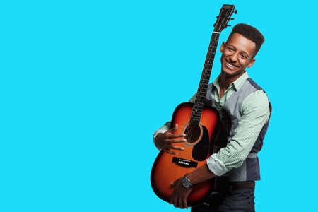 Stylish man with guitar in studio. Young smiling hipster man posing cheerfully with guitar in his arms on blue background, copy space.