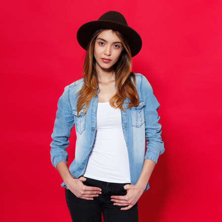 Close up of a stylish hot brunette girl wearing in hat and denim shirt, looking with attitude on camera, isolated over red background.