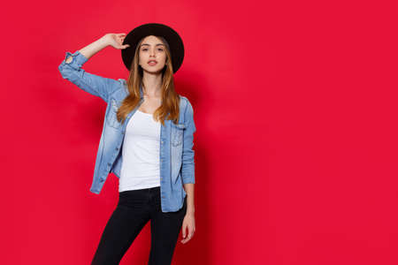 Lovely girl in casual clothes, holding a a hat with hands, standing and looking at camera isolated over red background. Place for copy space.