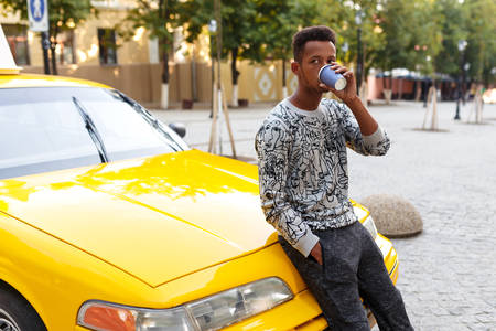 Mixed race male person drinking a cup o coffee, seated on the hood of a taxi, waiting outside.