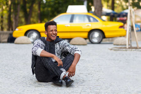 Young man seated down on pavement road with crossed legs, isolated on a yellow blurred taxi background, doing face grimace, laughing. Banco de Imagens