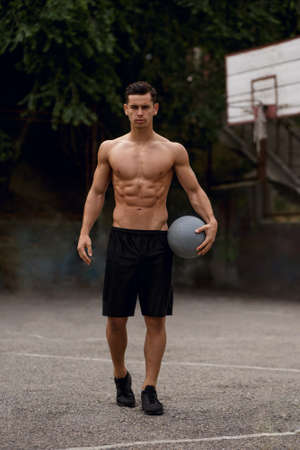 Frontal portrait of a fit, strong shirtless young man on a bascketball court, isolated on a street background.