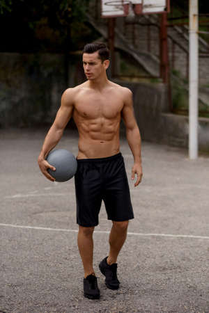 A fit sexy muscular male model standing on basketball court and holding a grey ball in hands, looking a side. Horizontal outside shot. Urban street background. Imagens