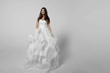 Charming young bride in luxurious wedding dress. Pretty girl in white princess bride dress. white background.
