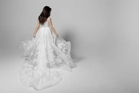 Back view of a elegantly female model in beautiful white wendding dress, isolated on a white background.