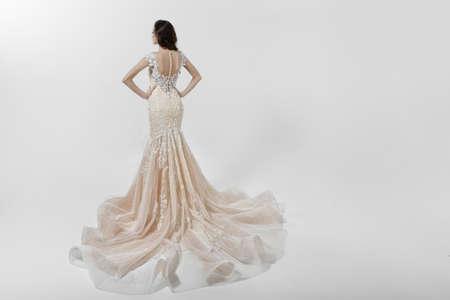 Vue arrière d'une fille de beauté aux cheveux longs bouclés en robe de mariée blanche avec broderie, isolée sur fond blanc.