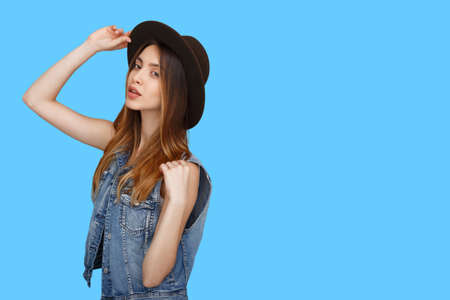Girl in casual clothes, holding a a hat with hands, standing and looking at camera isolated over blue background. Place for copy space.