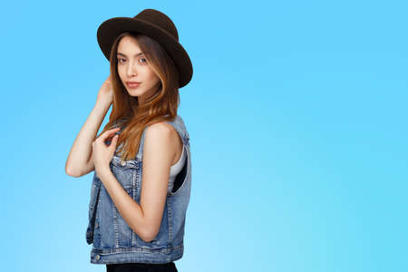 Cheerful girl in casual clothes, hat, standing in profile and looking, isolated over blue background.
