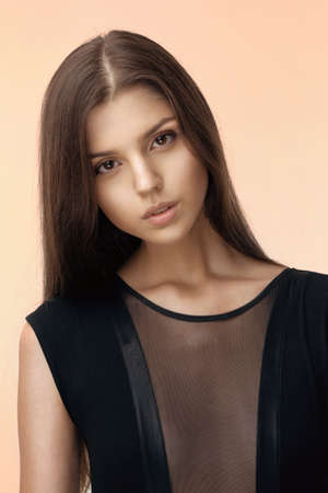 Portrait of young beautiful brunette girl in sensual black dress, looking at camera over beige background.