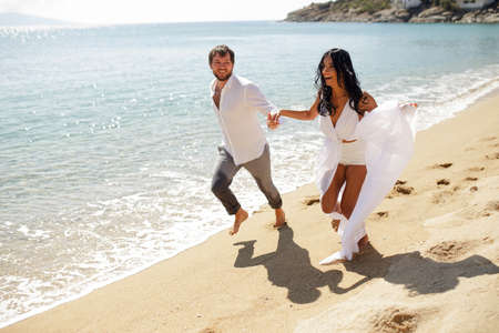 Happy couple just married young adults, men holding his wife passionately, running in the water, isolated on a seascape background. Imagens