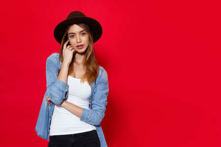 Stylish girl in casual clothes and brown hat, posing with attitudine in studio over light red background, with copy space. Model holding hands on keep hand under his face. Stock Photo