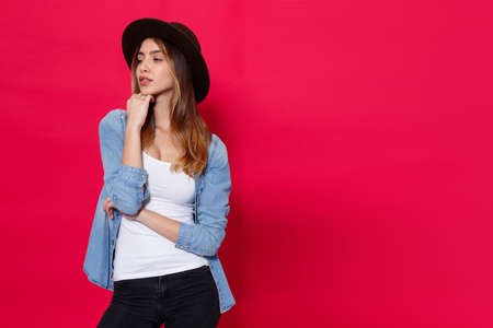 Fashionable girl in casual clothes and brown hat, posing with attitudine in studio over light red background, with place for text.