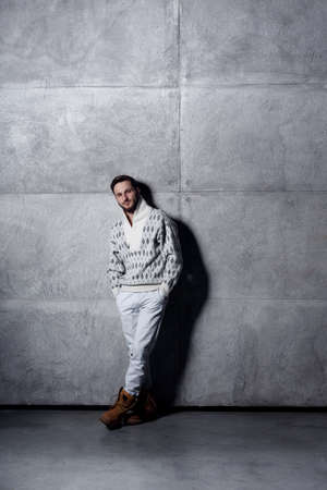 Vertical view of a guy in white jeans and sweater, posing in studio near concrete wall background. Imagens