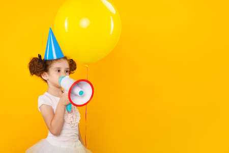 Funny little curly girl in white dress and blue birthday hat, shouting in megaphone over yellow background