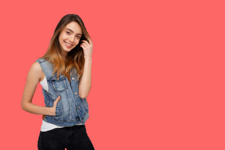 Hipster young woman in denim waistcoat, standing and looking at camera isolated over coral background. Copy space.