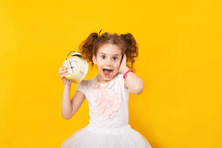 Little curly girl lying holding in one hands a big watches, another covering her ear not to hear alarm clock, have open mouth. Funny child in white dress, make a grimace, like screaming. Place with text.