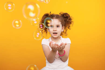 Image with little curly girl in studio over yellow backgrounds, catching soup bubbles, be amazed.